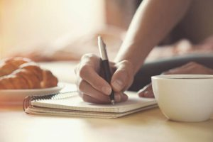 writing in journal with morning coffee